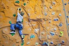 Rock-climbing boy with help stock photo