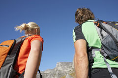 Rock climbing couple with rucksacks looking at rock in distance, rear view, close-up, low angle view Stock Photos