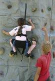 Rock climbing girl. Girl climbing up a rock wall stock photo