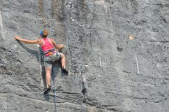 Rock Climbing Girl on rock face in red top. ROVINJ, ISTRIA, CROATIA - JUNE 25, 2017:  Rock Climbing Girl on rock face in red top Royalty Free Stock Image