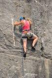 Rock Climbing Girl on rock face in red top. Stock Photos
