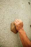 Rock climbing. Hand catchs stone on rock climbing wall Stock Image