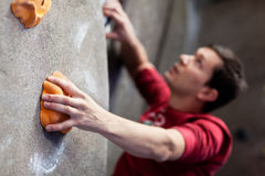 Rock climbing indoors. Young athlete rock climbing indoors royalty free stock images