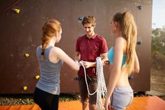 Rock climbing instructor is coaching how to tie knot. Male coach fixing rope into belay. Instructor preparing young Royalty Free Stock Photo