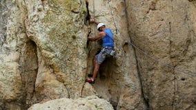 Rock climbing. Male hiker climbing on rock stock footage