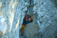Rock climbing. man rock climber climbing the challenging route on the rocky wall. Man rock climber in bright yellow shorts climbing the challenging route on the stock photo