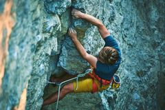 Rock climbing. man rock climber climbing the challenging route on the rocky wall. Man rock climber in bright yellow shorts climbing the challenging route on the stock photography