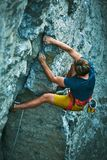 Rock climbing. man rock climber climbing the challenging route on the rocky wall. Man rock climber in bright yellow shorts climbing the challenging route on the stock images