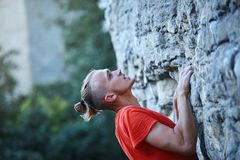 Rock climbing. man rock climber climbing the challenging route on the rocky wall. Man rock climber with long hair. close up side view of young man rock climber stock image