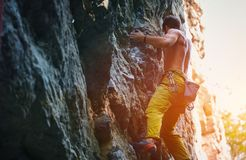 Rock climbing. man rock climber climbing the challenging route on the rocky wall. Muscular man rock climber in bright yellow pants climbing the challenging route stock image
