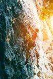 Rock climbing. man rock climber climbing the challenging route on the rocky wall. Muscular man rock climber in bright yellow pants climbing the challenging route stock photos