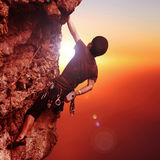 Rock climbing. Man climbing a mountain in the sunset light Royalty Free Stock Photos