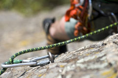 Rock climbing man on a rock. Detail of carbine with rope on a rock Stock Photo