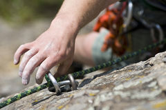 Rock climbing man on a rock. Hand of climbing man with carbine and rope Royalty Free Stock Photography