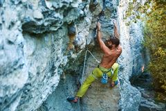 Rock climbing. man rock climber climbing the challenging route on the limestone wall. Muscular man rock climber in bright yellow pants climbing the challenging stock images