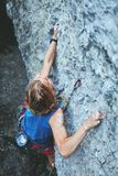 Rock climbing. man rock climber climbing the challenging route on the rocky wall. Man rock climber with long hair. top view of young man rock climber in bright stock photo