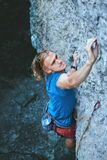 Rock climbing. man rock climber climbing the challenging route on the rocky wall. Man rock climber with long hair. top view of young man rock climber in bright stock photography
