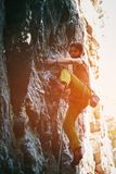 Rock climbing. man rock climber climbing the challenging route on the rocky wall. Muscular man rock climber in bright yellow pants climbing the challenging route royalty free stock photos