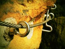 Rock climbing safety path via ferrata. Steel chrome anchores in rock hold steel twisted rope Royalty Free Stock Photo