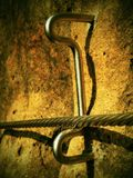 Rock climbing safety path via ferrata. Steel chrome anchores in rock hold steel twisted rope Royalty Free Stock Images