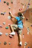 Rock Climbing Series A 10. A young girl climbing a tall, indoor, man-made rock climbing wall Royalty Free Stock Photography
