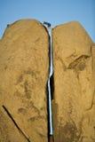 Rock climbing a split pillar. Stock Photo