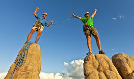 Rock climbing team reaching the summit. Team of climbers celebrate on the summit of a rock pinnacle after a challenging ascent Stock Photography