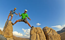 Rock climbing team reaching the summit. Royalty Free Stock Image