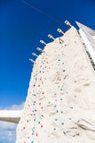 Rock Climbing Wall Under Blue Sky with Bell at Top Royalty Free Stock Photography