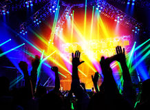 Rock concert. Happy people silhouettes, raise up hands, disco party with large group of dancing man, bright colorful stage lights, active lifestyle, music Stock Photography