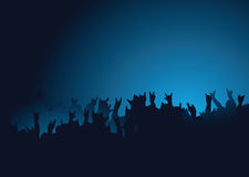 Rock concert. Hands raised at a rock concert with the crown back lit in blue Royalty Free Stock Photo