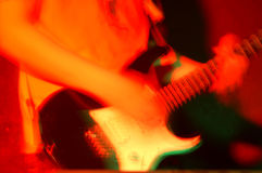 Rock concert. A guitar player in action, blurred motion, defocused, red lights Stock Images