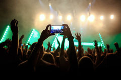 Rock concert crowd recording performance with digital smartphone. Green guitar in stage Royalty Free Stock Photography