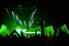 Rock concert crowd recording performance with digital smartphone. Green guitar in stage Stock Photography