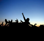 Rock Concert Crowd Surf. Silhouette of a a young man surfing the crowd at an open air rock festival Royalty Free Stock Photography