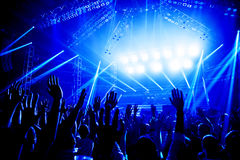 Rock concert. Crowd of young people enjoying night performance, raised up and clapping hands, dance club, bright blue lights, music entertainment Stock Images
