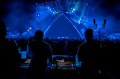 Rock Concert with Empty Stage. Large crowd looking towards empty stage with sound engineers and mixing desk in foreground Royalty Free Stock Image