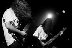 Rock concert, guitar music. Two guitarists playing heavy metal, rock music on stage live with long hair and classical rockstar looks. Monochrome black and white Royalty Free Stock Photography