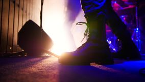 Rock concert. Guitarist in black massive boots playing guitar. Feet close up. Shot royalty free stock photography