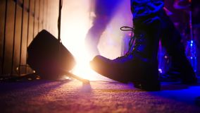 Rock concert. Guitarist in black massive boots playing guitar on stage. Feet close up. Shot stock photo