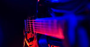 Rock concert. Guitarist plays the guitar. The guitar illuminated with bright neon lights. Focus on strings. No face shown stock photography