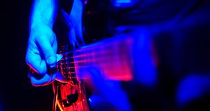 Rock concert. Guitarist plays the guitar. The guitar illuminated with bright neon lights. Hand close up. Shot royalty free stock photos
