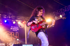Rock concert. A guitarist plays in a heavy metal rock concert, holding an electric guitar and colorful lighting on the stage Royalty Free Stock Photos