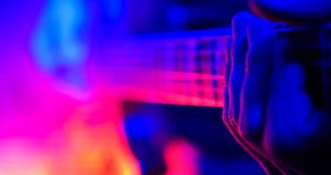 Rock concert. Guitarist plays on the illuminated lamps guitar. Hand close up. Shot royalty free stock photo