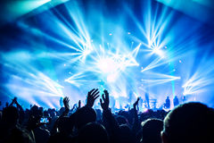 Rock concert. Large group of happy people enjoying rock concert, clapping with raised up hands, blue lights from the stage, new year celebration concept