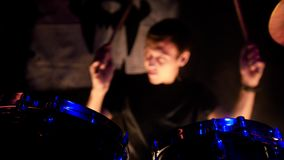 Rock concert. A man playing drums on stage. The drummer holding drumsticks. Drums close up. Shot stock photos