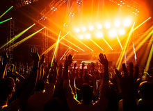 Rock concert. Photo of young people having fun at rock concert, active lifestyle, fans applauding to famous music band, nightlife, dj on the stage in the club Stock Photo