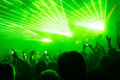Rock concert, silhouettes of happy people raising up hands. In front of bright, green stage laser lights. Space in top side Stock Images