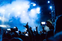 Rock concert, silhouettes of happy people raising up hands Stock Photo
