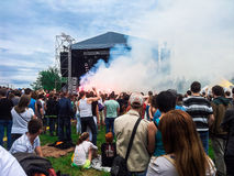 Rock concert under the open sky. Rock festival, spectators, concert hall, lit flares and smoke bombs. Vacationers people royalty free stock images